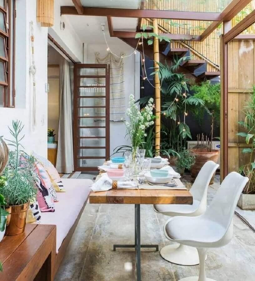 varanda decorada com cadeiras brancas e mesa com banco estofado Foto Histórias de Casa