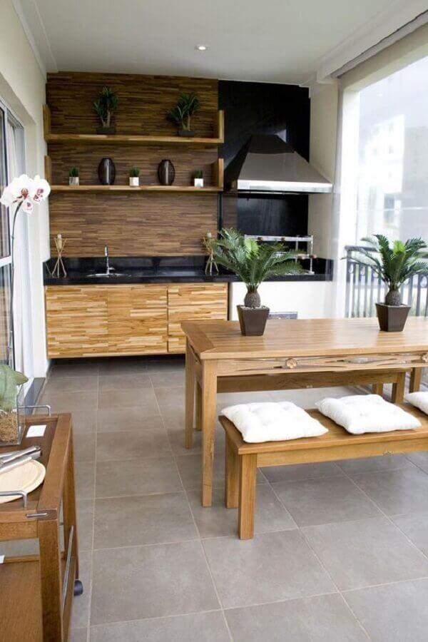 varanda gourmet com churrasqueira decorada com mesa com banco de madeira Foto Casa Três Chic