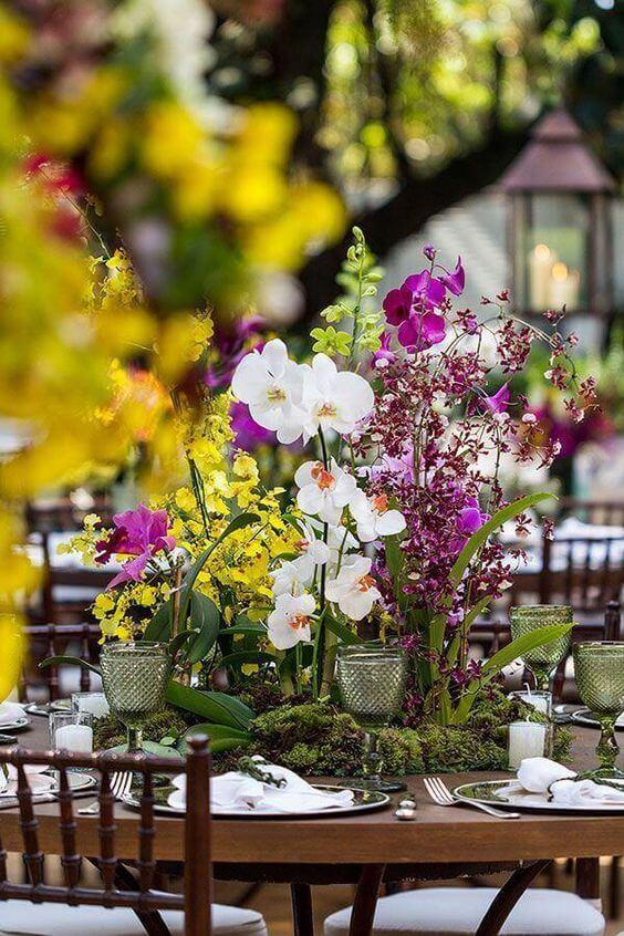 Vaso com flor roxa e branca na decoração de festa