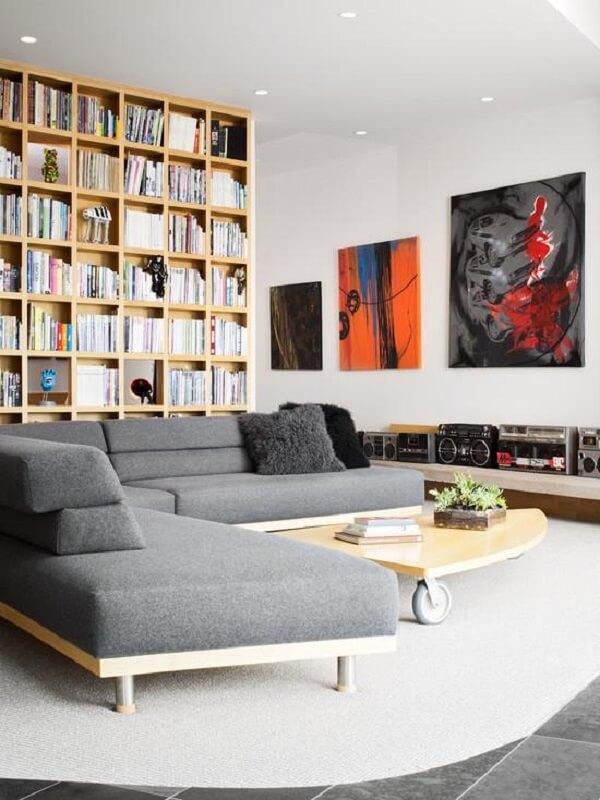 A base em madeira deixa o sofá de canto cinza mais moderno