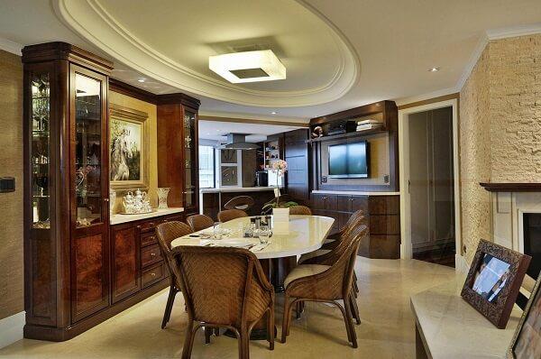 A cristaleira de madeira auxilia na organização de taças e copos da sala de jantar