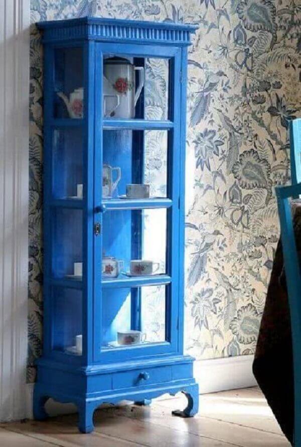 A cristaleira de madeira azul se destaca na decoração