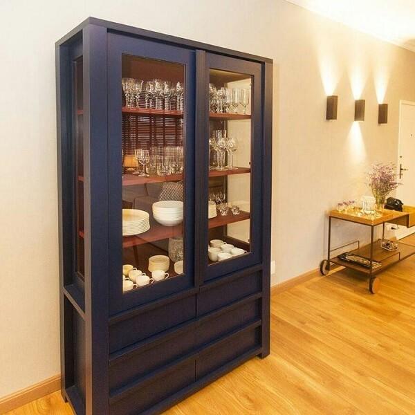 A cristaleira de madeira com vidro permite que os utensílios de cozinha sejam vistos de fora do móvel