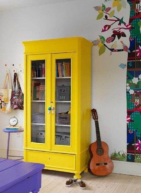 A cristaleira de madeira em tom amarelo traz alegria para o espaço