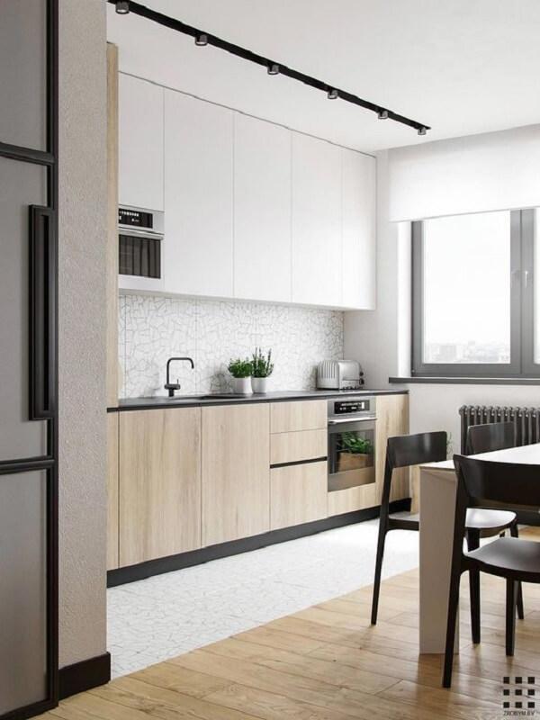 A luminária de trilho preta da cozinha se destaca no teto branco