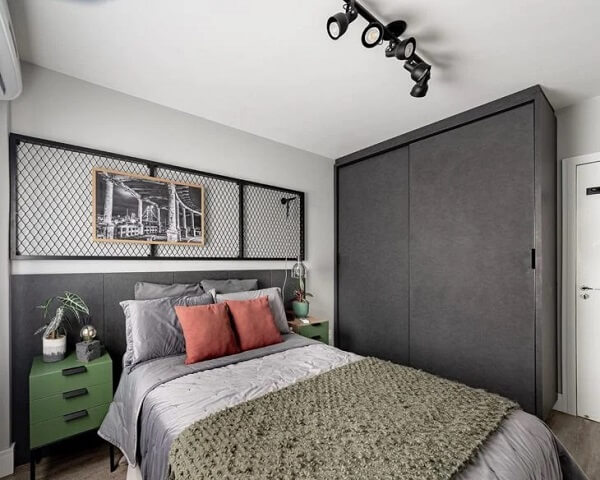 A luminária trilho fixada no teto acima da cama auxilia na iluminação de todo o ambiente
