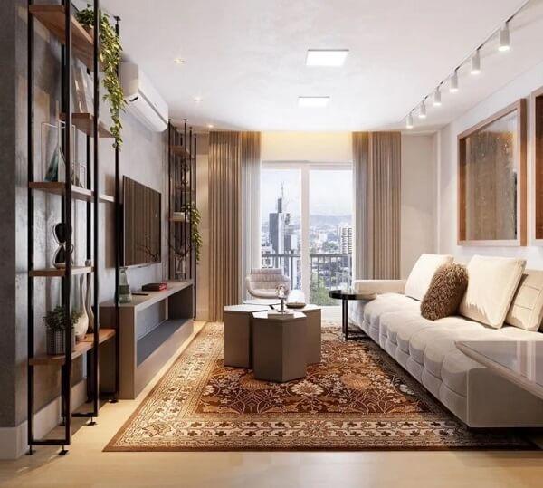 A luminária trilho na sala de estar destaca a presença do sofá branco