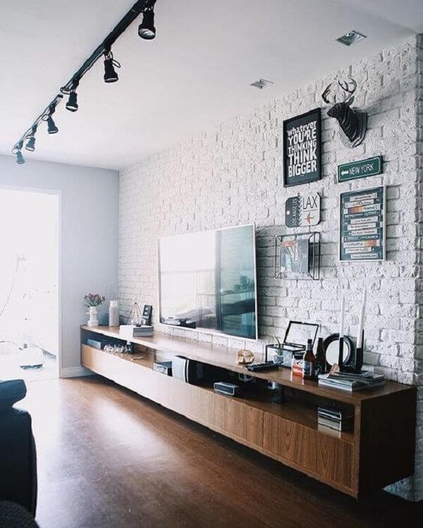 A luminária trilho preta fixada no teto se estende por toda a sala de estar