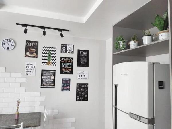 A luminária trilho realça a presença dos quadros na cozinha