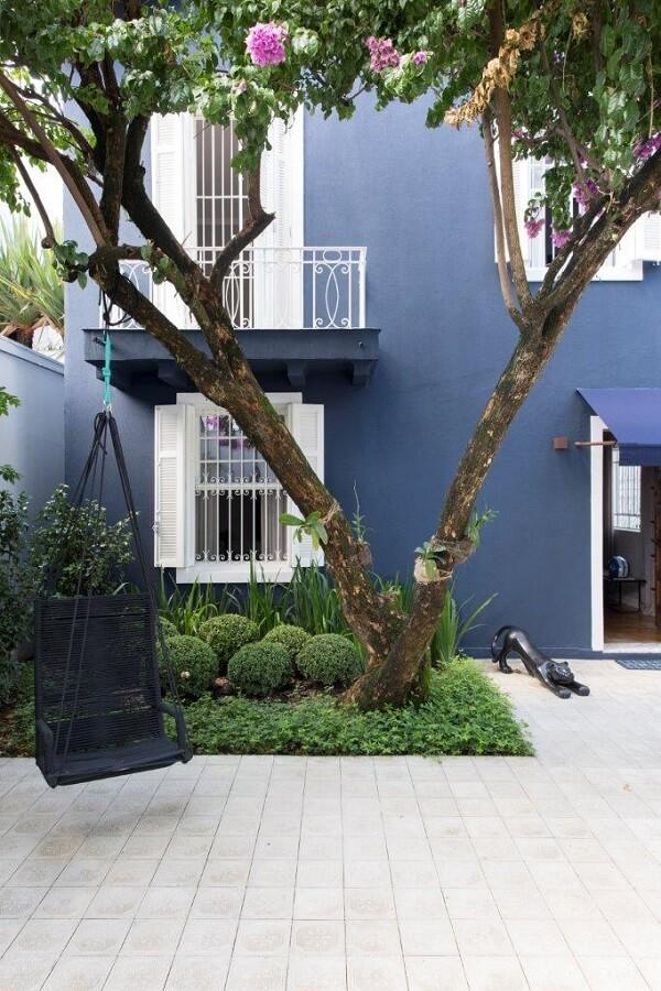 A rede cadeira traz um toque aconchegante para o quintal da casa simples. Fonte: Two Design