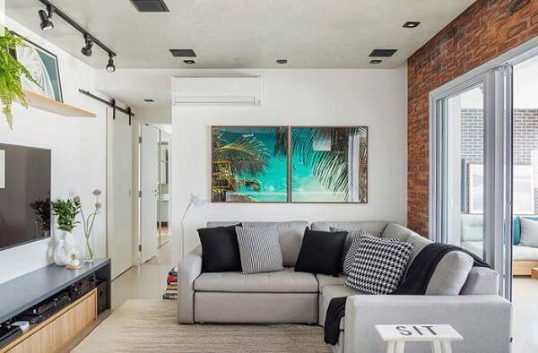 A sala de tv fica ainda mais aconchegante com a presença do sofá de canto cinza