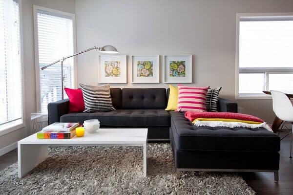As almofadas coloridas se destacam sobre o sofá de canto cinza escuro