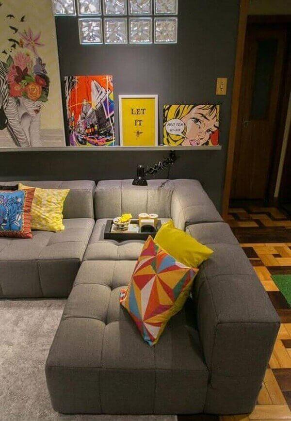 As almofadas coloridas se destacam sobre o sofá de canto cinza