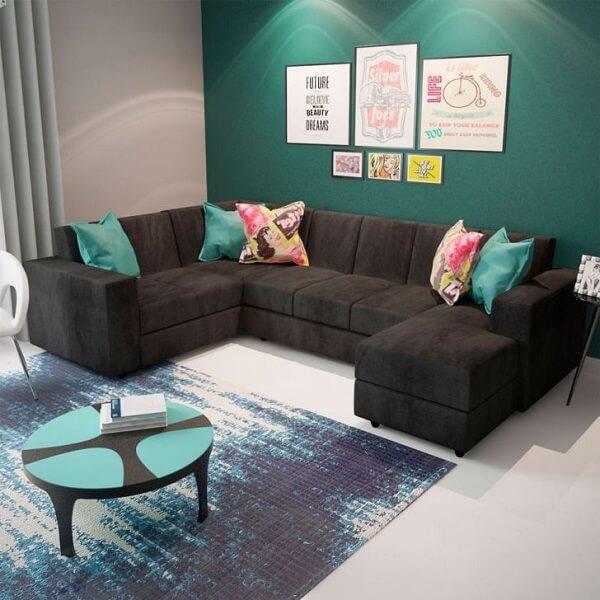 As almofadas coloridas sobre o sofá de canto cinza escuro trazem alegria para o ambiente