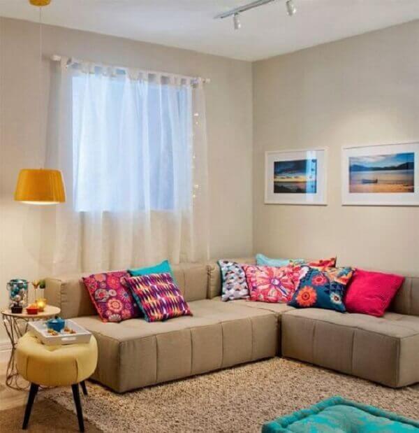 As almofadas coloridas sobre o sofá de canto cinza trazem alegria para o espaço