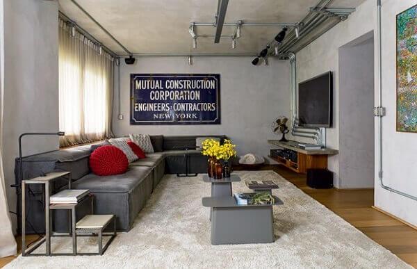 As almofadas vermelhas quebram a neutralidade do sofá de canto cinza