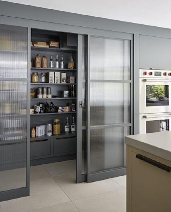 As portas de vidro escondem parcialmente a despensa de cozinha