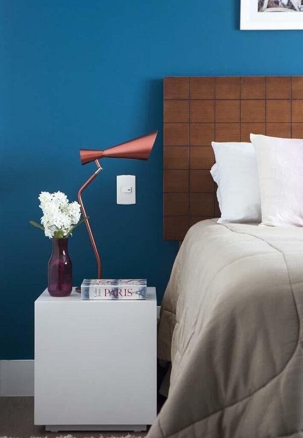 As roupas de cama em tons claros traz neutralidade para o quarto com parede azul