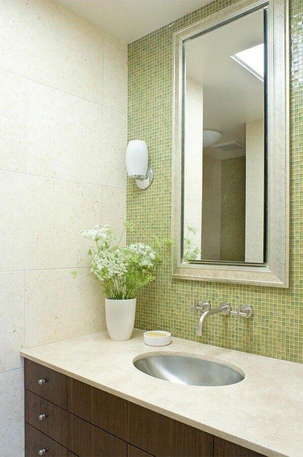 Banheiro com pastilha adesiva de vidro verde ao redor do espelho