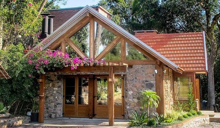 Casa simples com parede de pedra e pergolado de madeira. Fonte: Homify