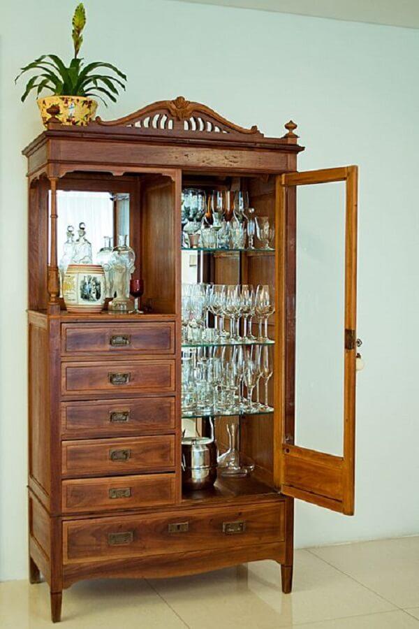 Cristaleira de madeira com 1 porta de vidro e várias gavetas