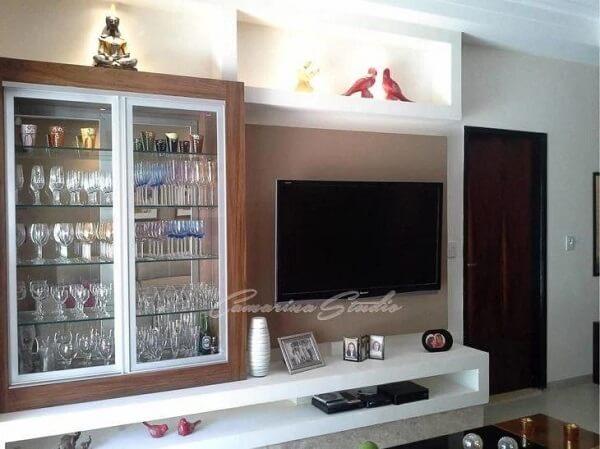 Cristaleira de madeira com prateleira de vidro embutida no painel de TV