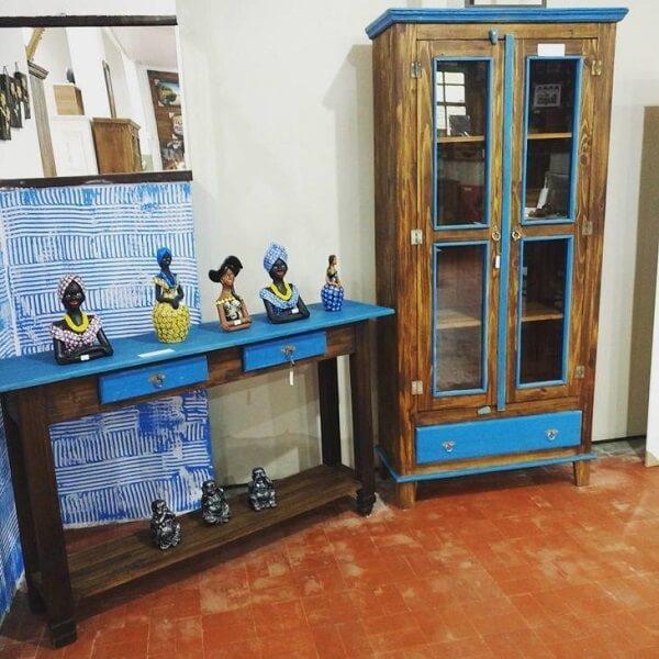 Cristaleira de madeira de demolição com detalhes em azul que se conectam com o aparador
