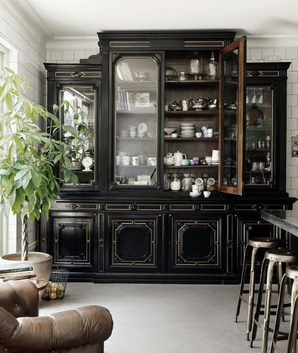Cristaleira de madeira em tom preto se destaca na decoração