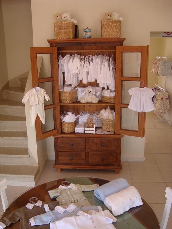Cristaleira de madeira usada para mostruário de roupas de bebe