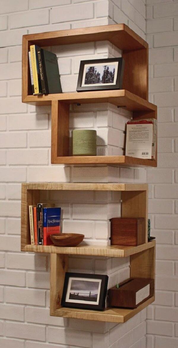 Esse modelo de nicho de canto de madeira abraça a parede e serve de apoio para diversos itens de decoração