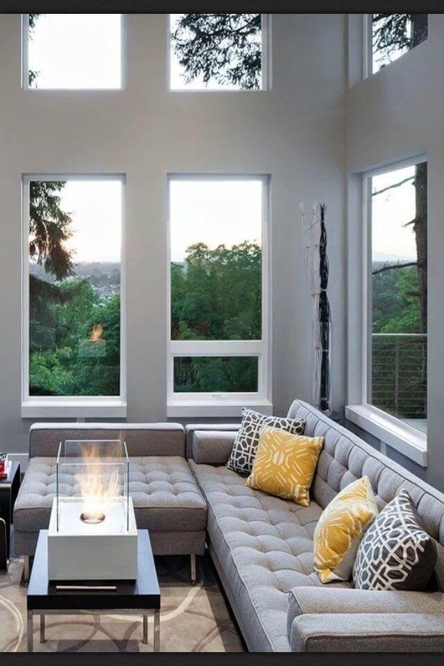 Esse modelo de sofá de canto cinza acomoda vários pessoas no local
