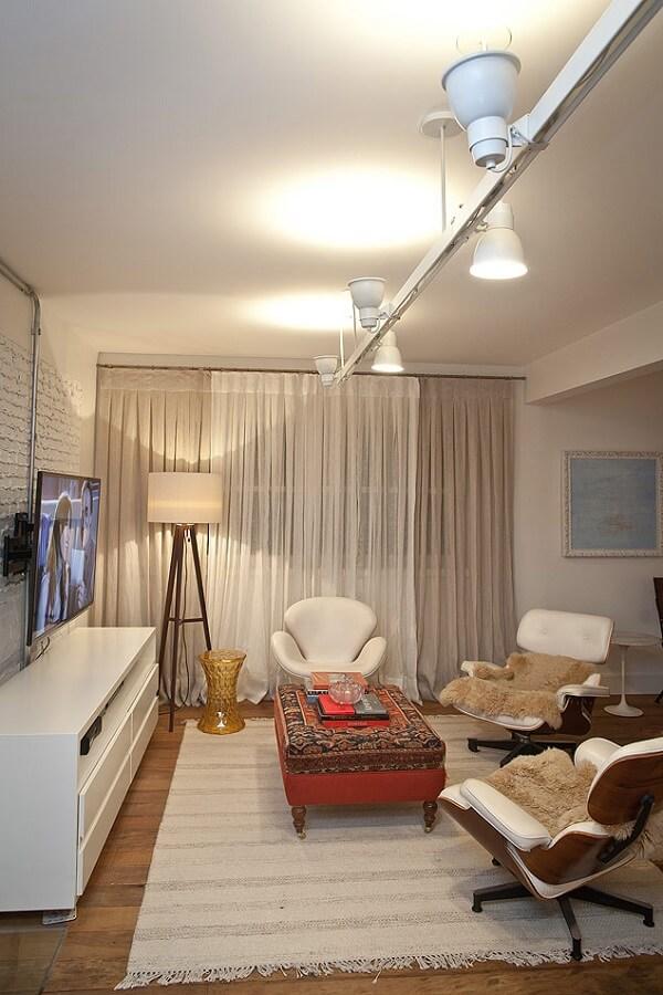 Luminária trilho branca com fachos de luz direcionados para o chão e teto