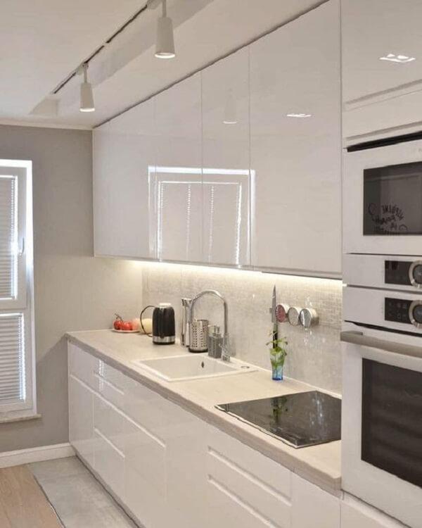 Modelo de luminária trilho para cozinha branca se conecta com o restante da decoração