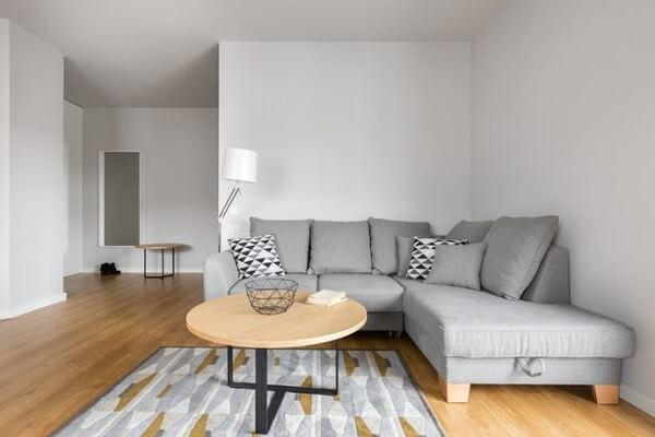 Modelo de sofá de canto cinza com chaise conta com acabamento em madeira