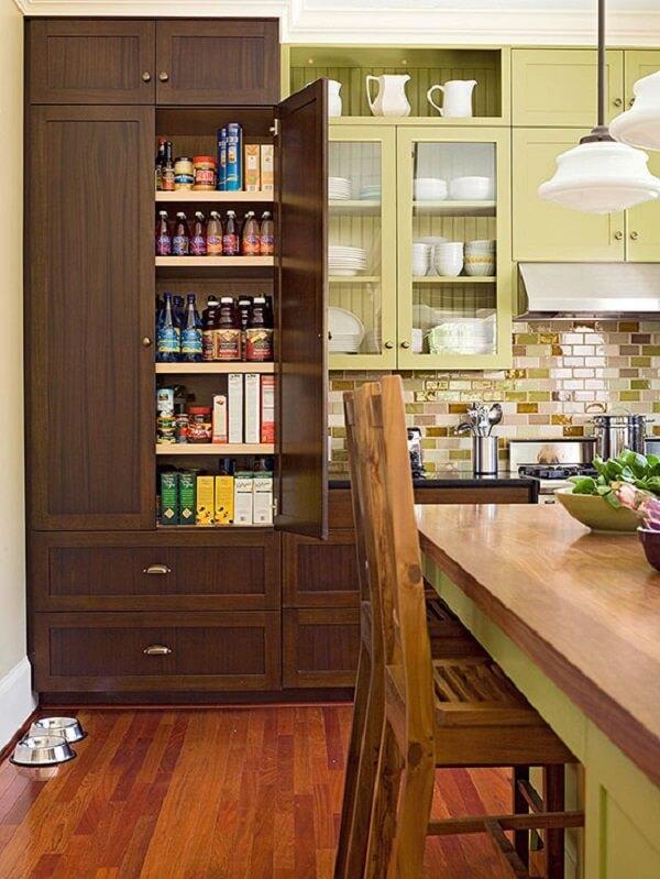 O armário para despensa de cozinha feito em madeira escura se destaca na decoração do ambiente