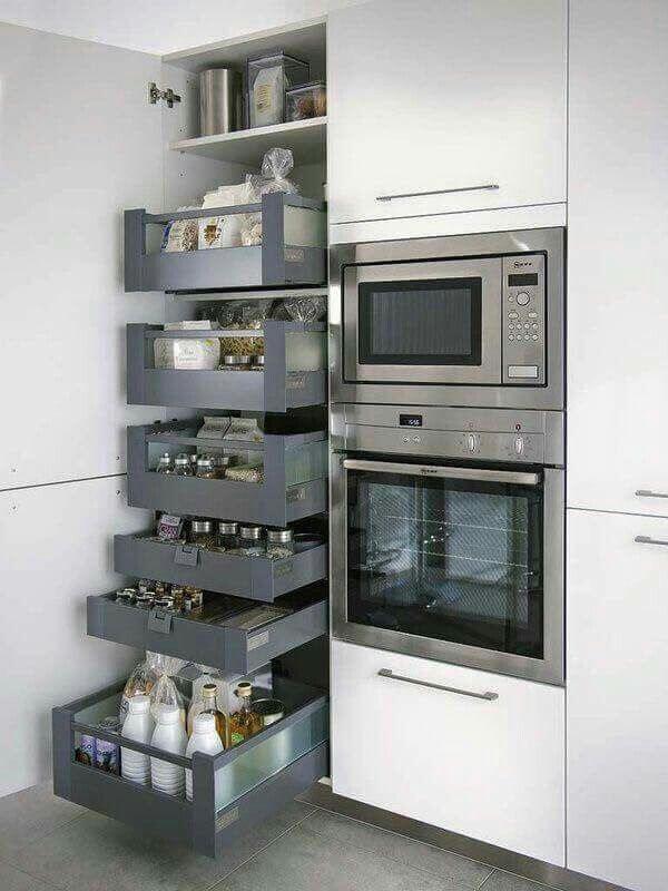 O armário para despensa de cozinha fica ao lado dos eletrodomésticos do espaço