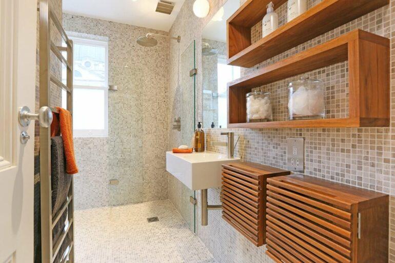O nicho de madeira retangular auxilia na organização do banheiro