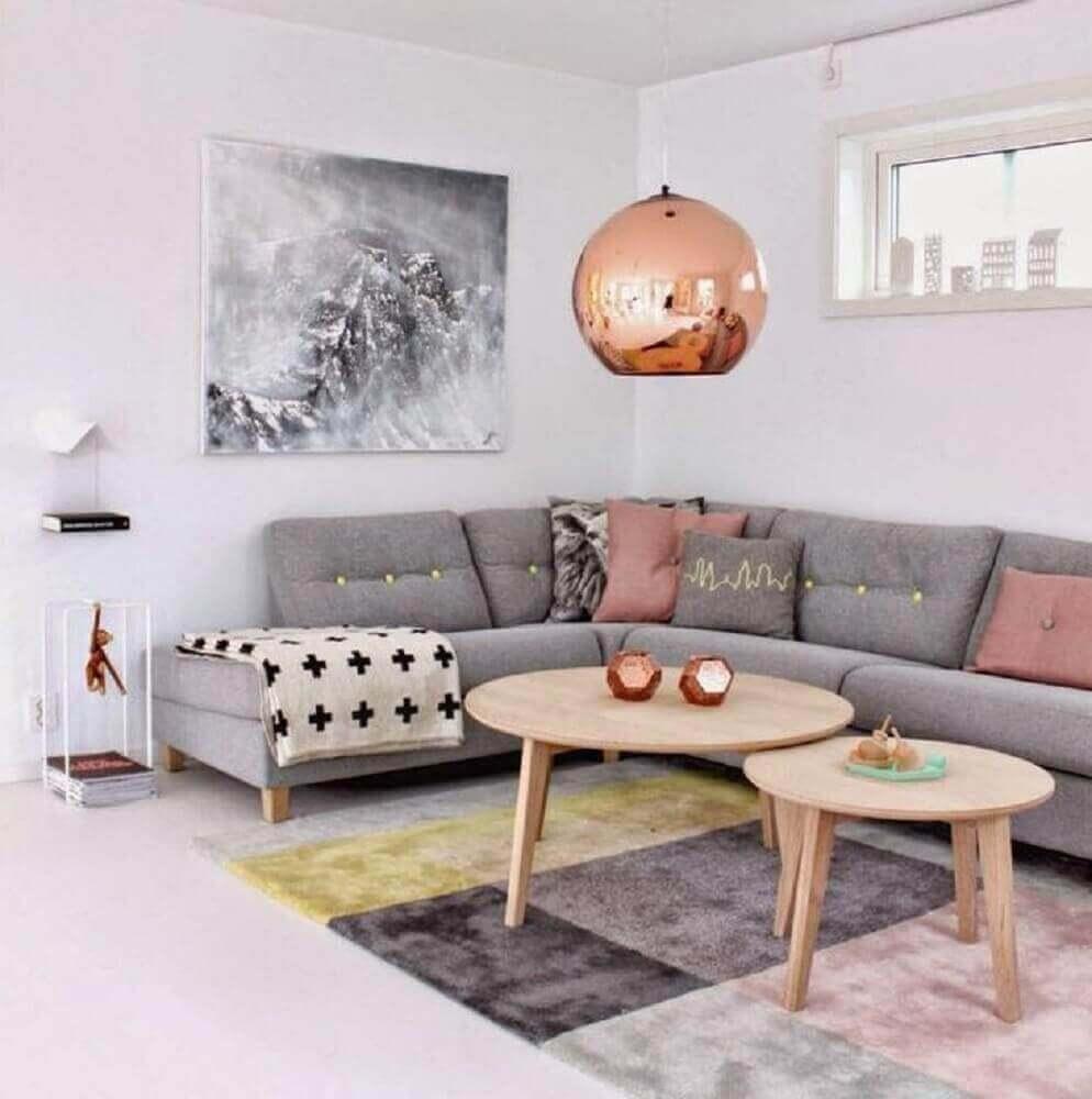 O pendente rosa se destaca na decoração dessa sala com sofá de canto cinza