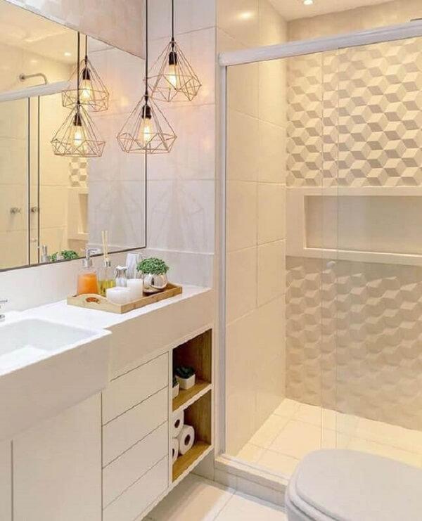 O revestimento 3D para banheiro e os pendentes aramados complementam a decoração