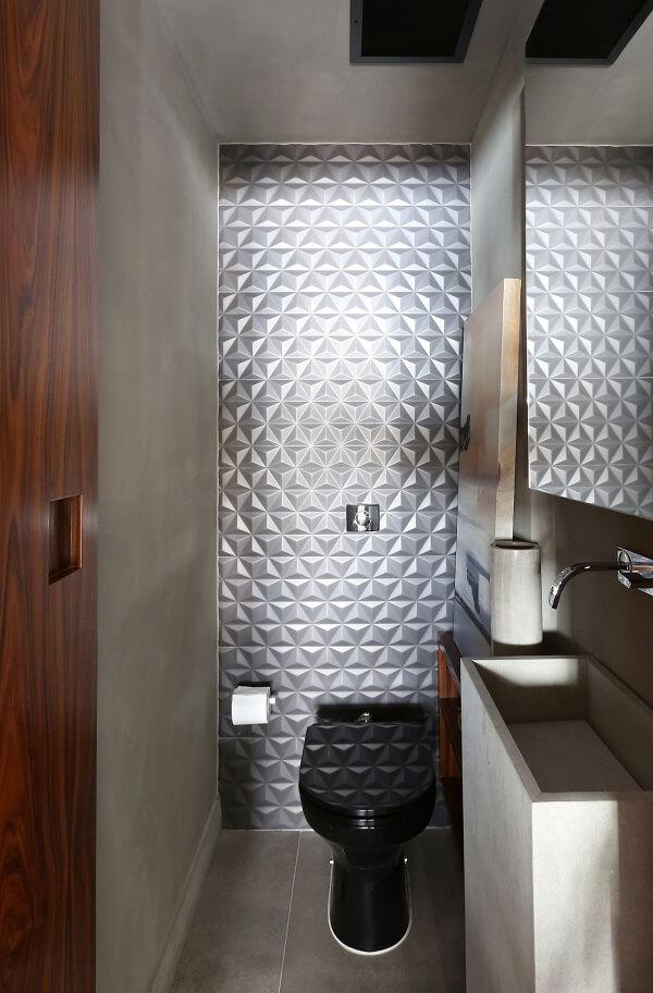 O revestimento 3D para banheiro pequeno metalizado é o grande destaque desse espaço