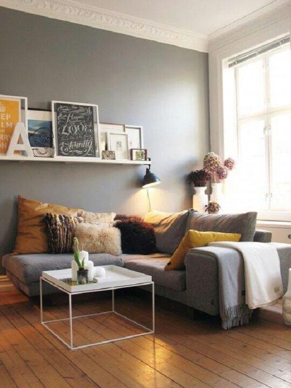 O sofá de canto cinza claro foi alinhado rente a parede e a janela do ambiente
