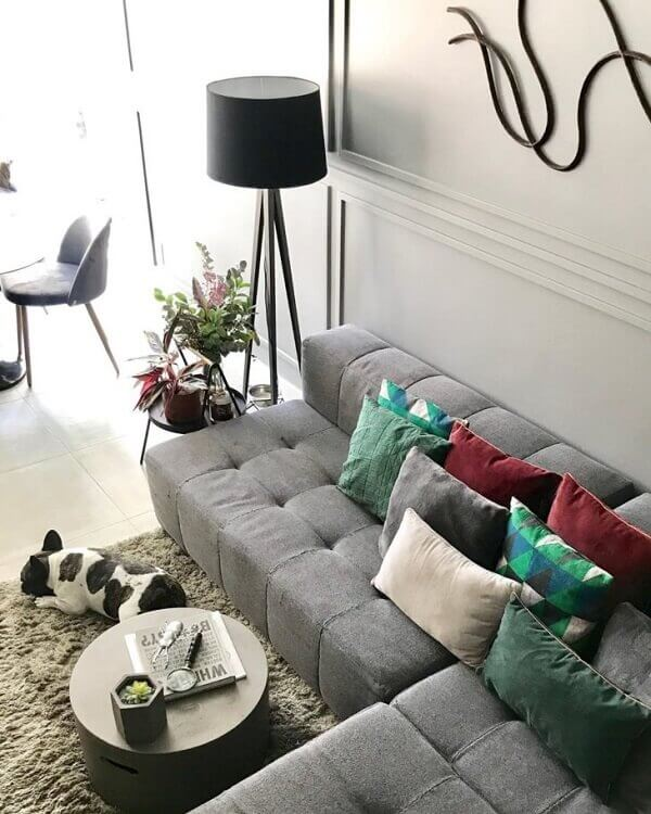 O sofá de canto cinza claro traz conforto aos usuários