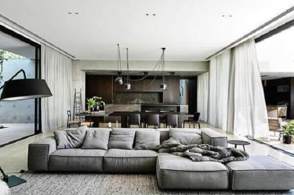 O sofá de canto cinza delimita a área da sala de estar