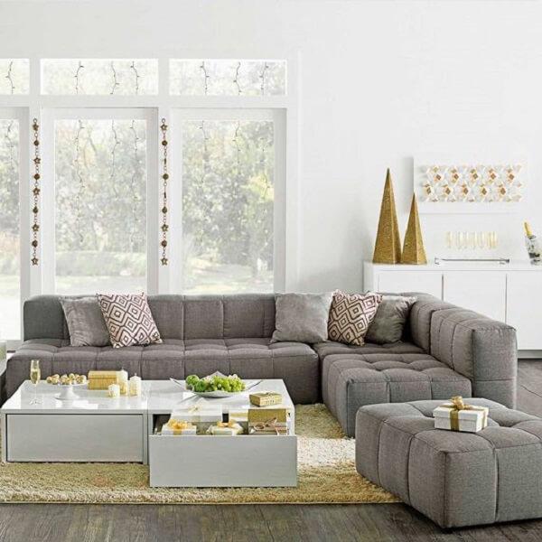 O sofá de canto cinza delimita a área da sala