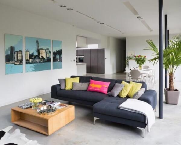 O sofá de canto cinza escuro se conecta com o piso em cimento queimado
