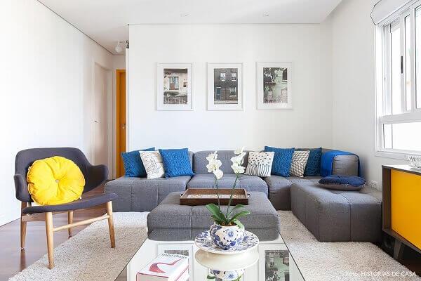 O sofá de canto cinza modulado foi alinhado rente a parede do cômodo