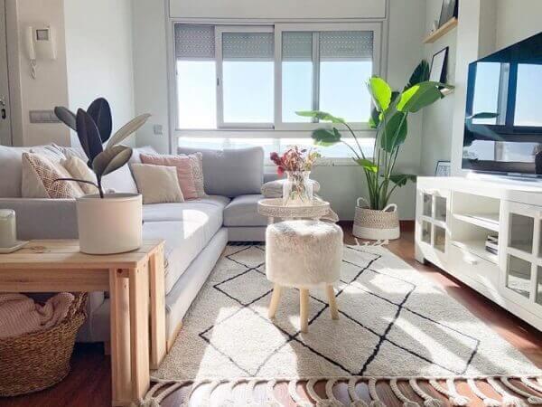 O sofá de canto cinza preenche graciosamente a sala de estar