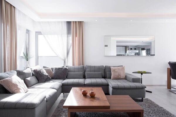 O sofá de canto cinza preenche toda a sala de estar e acomoda várias pessoas