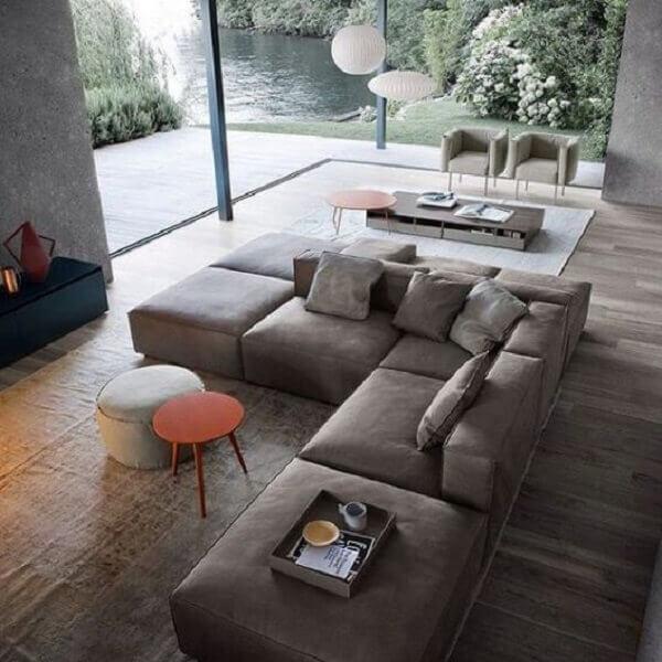 O sofá de canto cinza separar os ambientes integrados e acomoda várias pessoas
