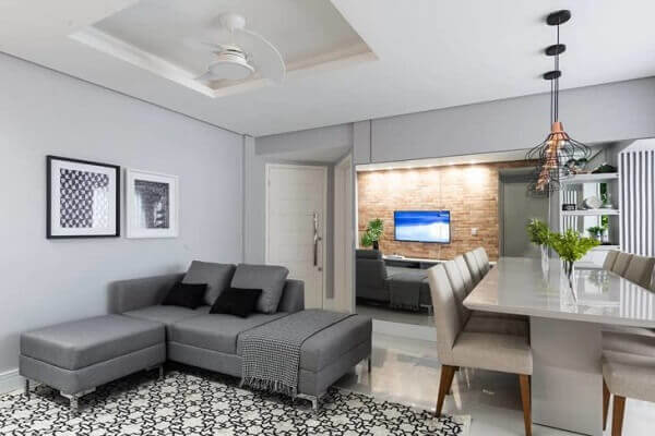O sofá de canto pequeno cinza separa ambientes integrados